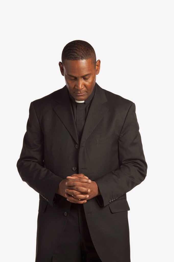 Stock Photo: 1889R-51859 a man wearing a clerical collar with his head bowed in prayer