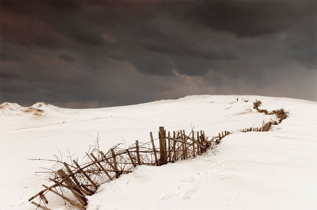 a broken fence in a snowy field with a dark sky above : Stock Photo