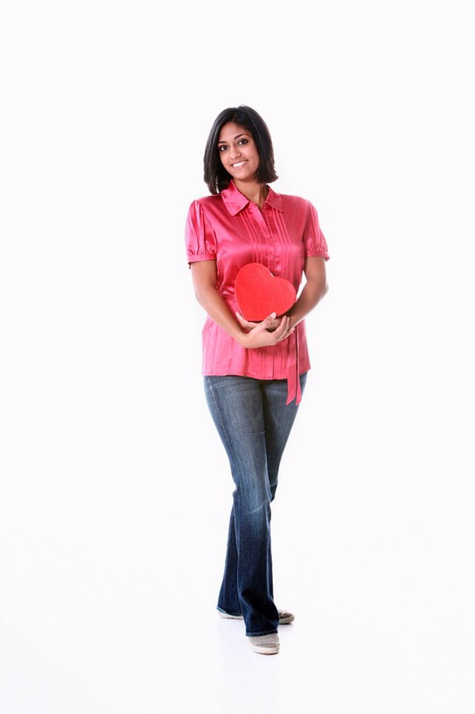 a young woman holding a heart in her arms : Stock Photo