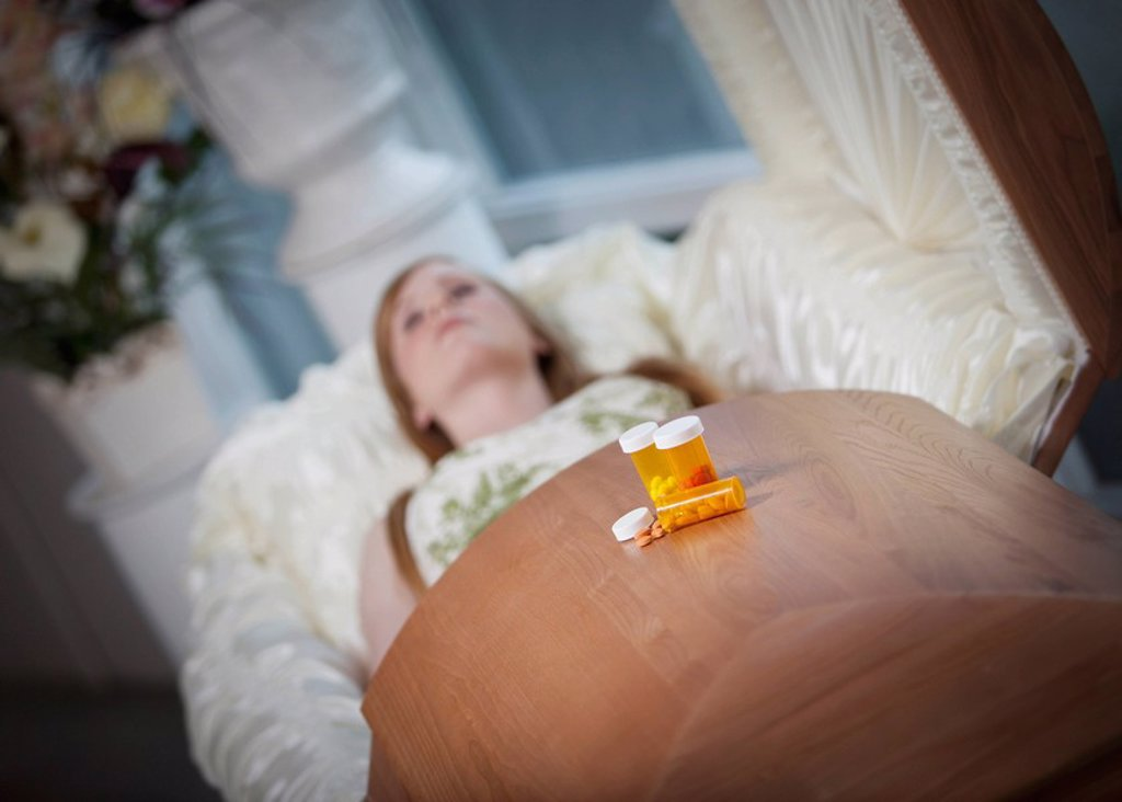 Stock Photo: 1889R-52160 the coffin of a young woman with medication bottles on top