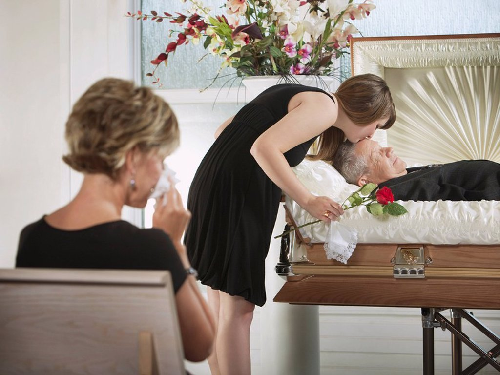 Stock Photo: 1889R-52259 a young woman kissing a loved one in a coffin at a funeral