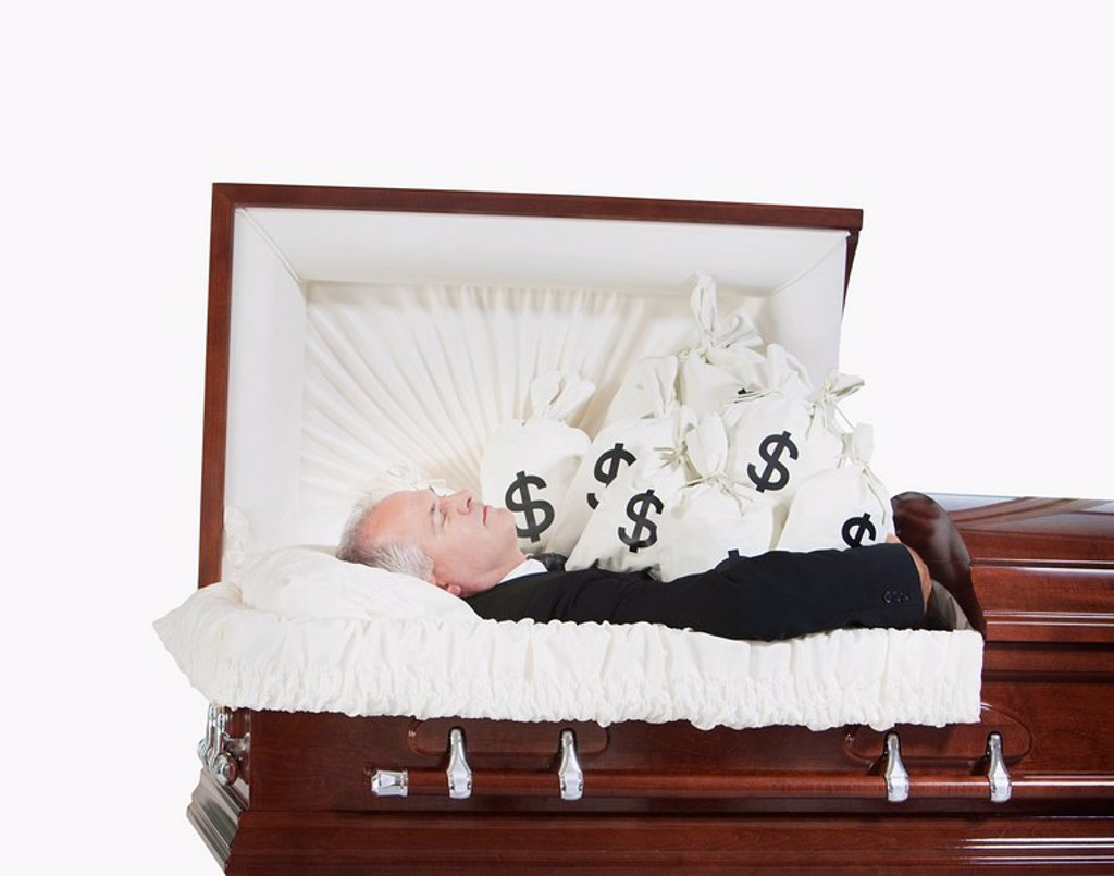 Stock Photo: 1889R-52269 a deceased man in a coffin surrounded by bags of money