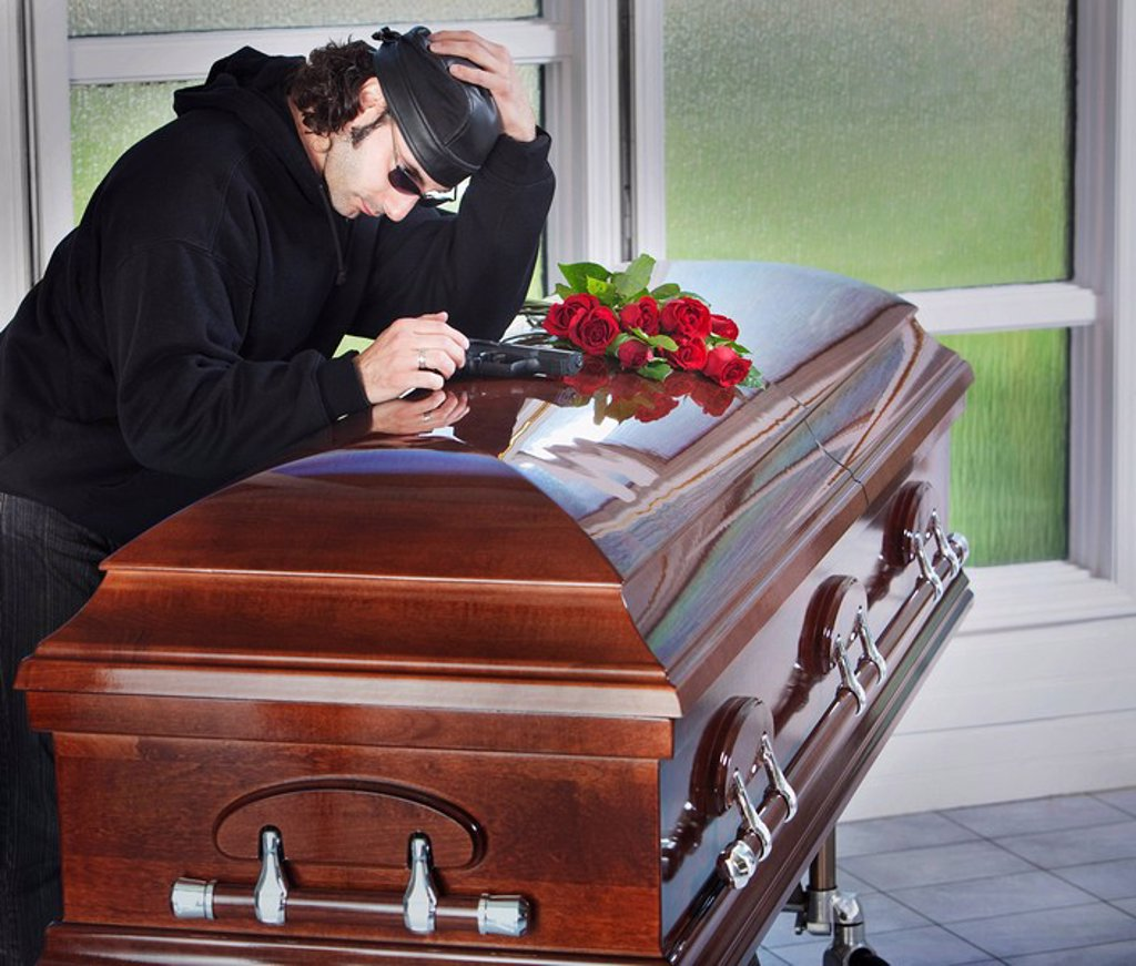 a man laying his gun on top of a coffin : Stock Photo