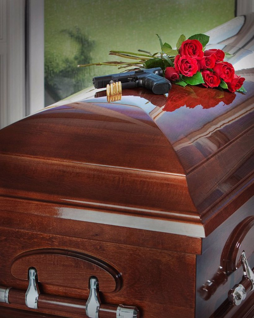 a gun, bullets and bouquet of roses on top of a coffin : Stock Photo