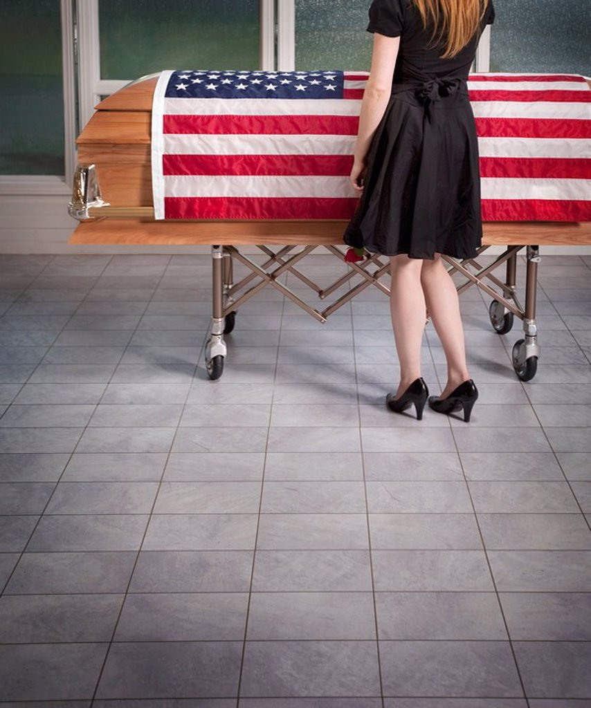 paying respects to the deceased with an american flag draped over the coffin : Stock Photo