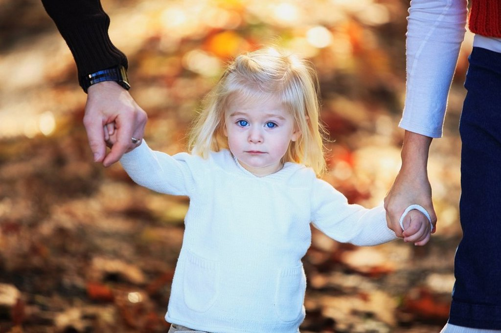 Stock Photo: 1889R-52549 a young girl holding the hands of her parents