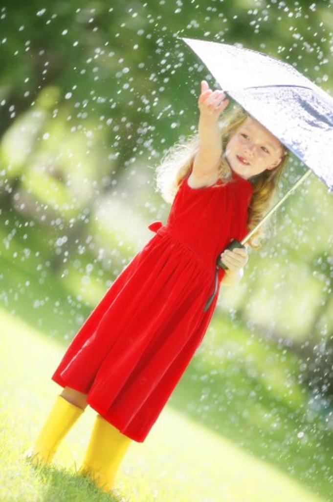 A little girl walking in the rain : Stock Photo
