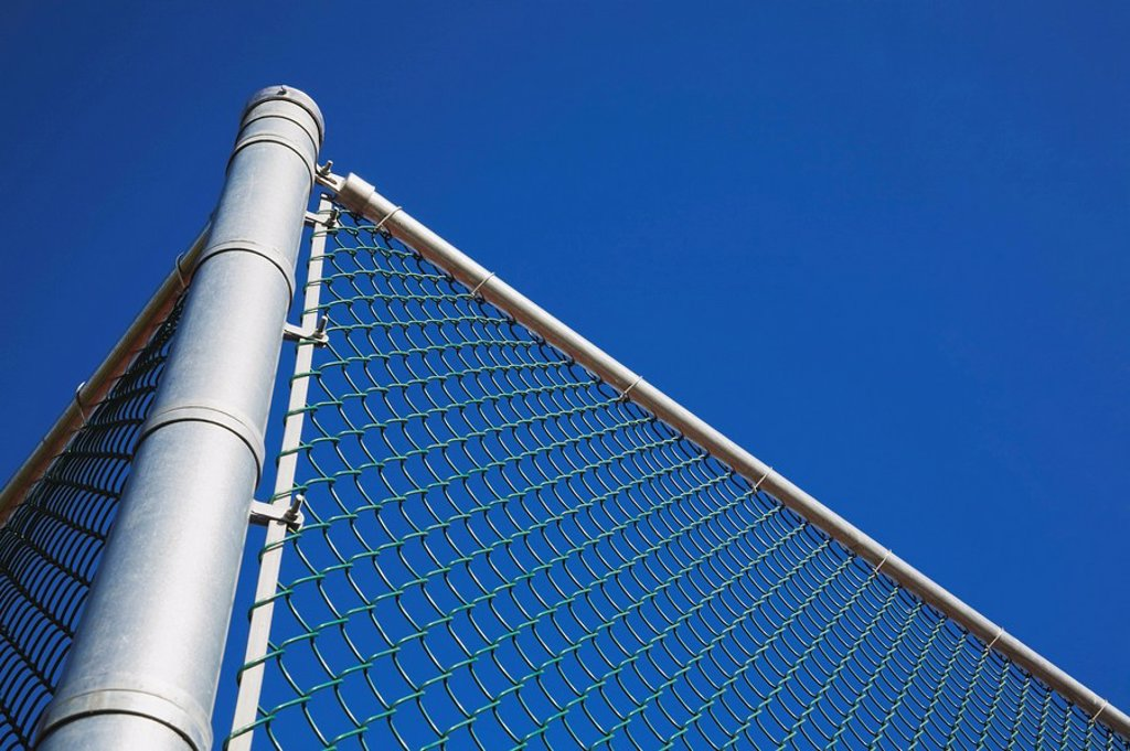 metal post with a chain link security fence against a blue sky : Stock Photo
