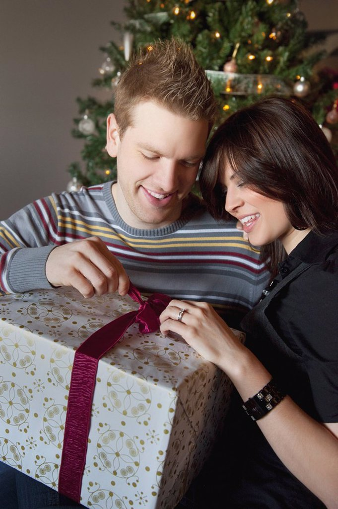 a couple opening a gift by the christmas tree : Stock Photo