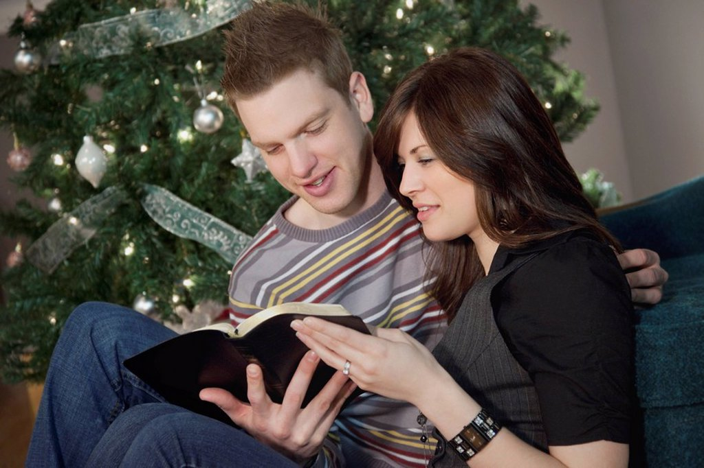 a couple reading the bible by the christmas tree : Stock Photo