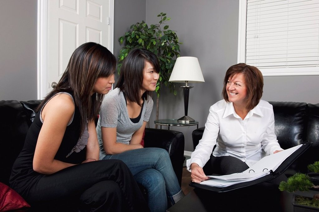 Stock Photo: 1889R-53025 a businesswoman showing two young women a document