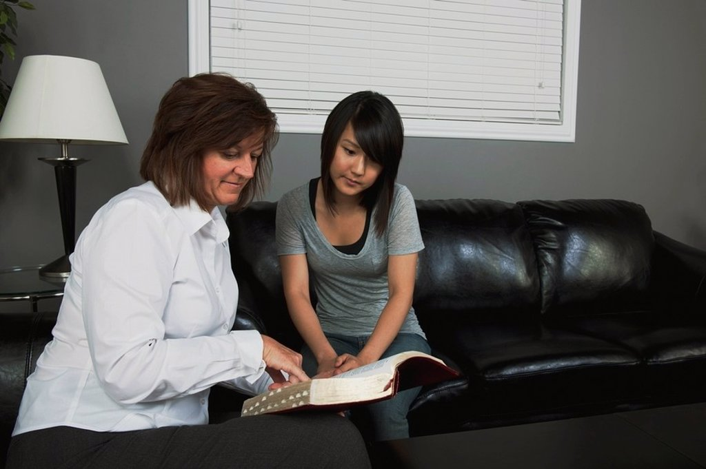 a woman showing a bible passage to a young woman : Stock Photo