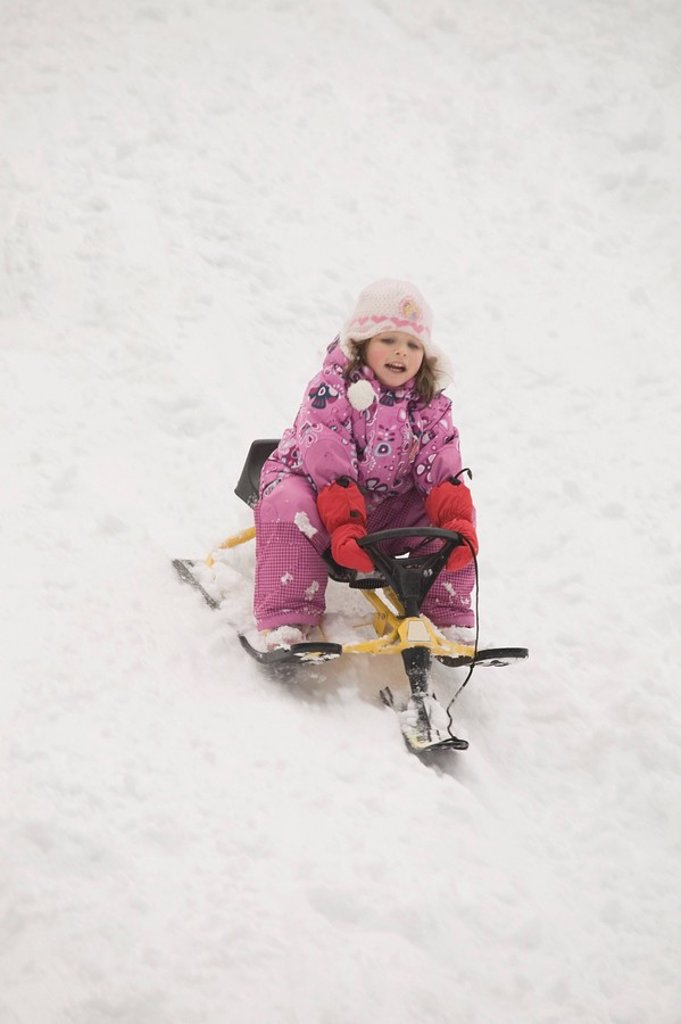 blairmore, alberta, canada, young girl sledding down a hill : Stock Photo