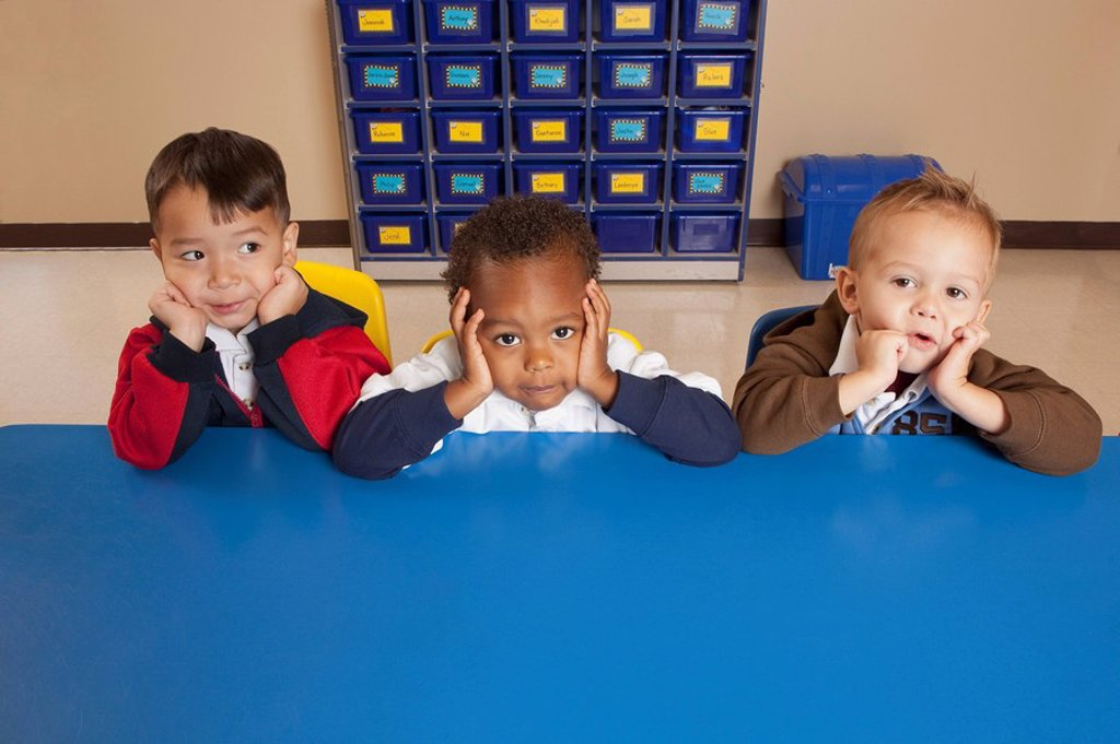 Stock Photo: 1889R-53242 fort lauderdale, florida, united states of america, three young boys sitting at a table in a classroom