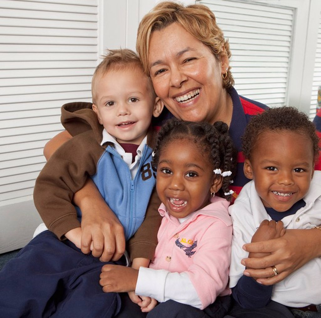 fort lauderdale, florida, united states of america, a teacher hugging three young children : Stock Photo