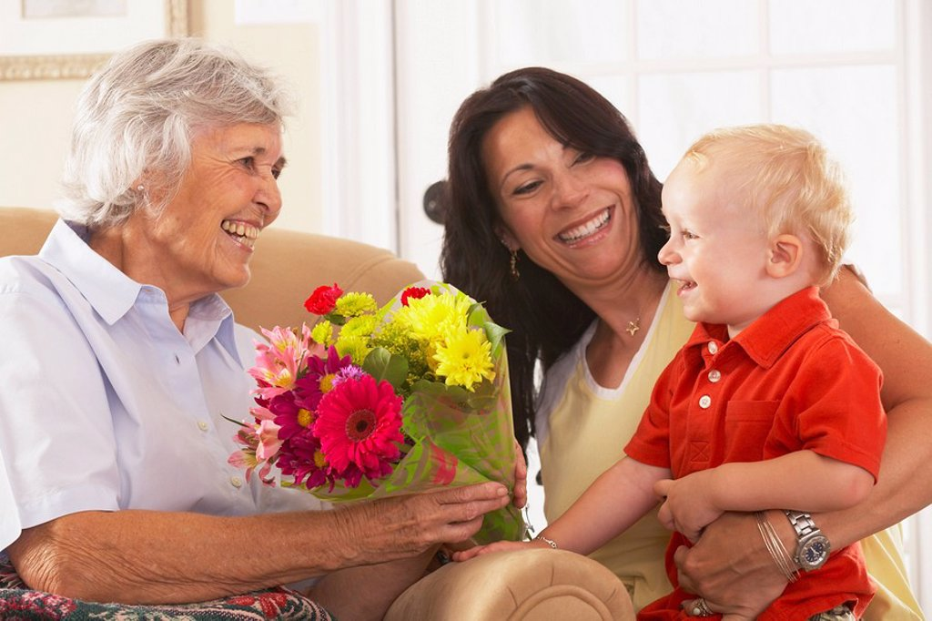 a young child giving flowers to his grandmother : Stock Photo