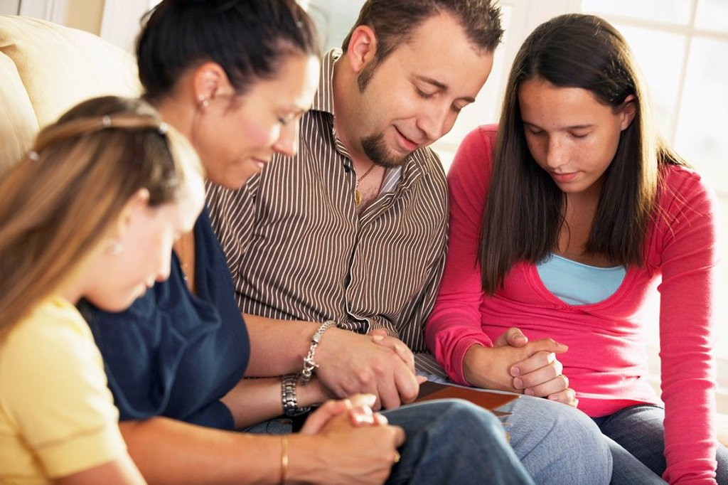 Stock Photo: 1889R-53394 a family praying together