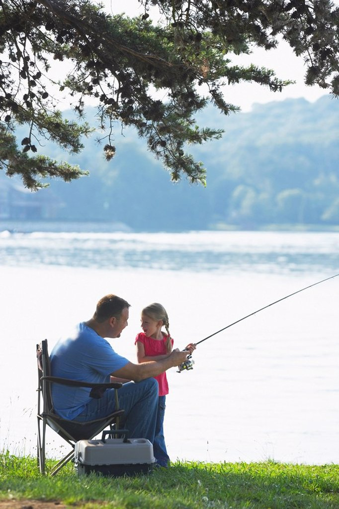 a father and daughter fishing together : Stock Photo