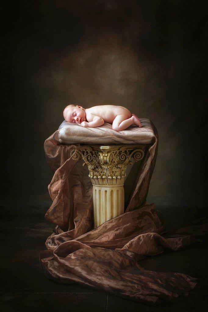a baby asleep on a pillar : Stock Photo