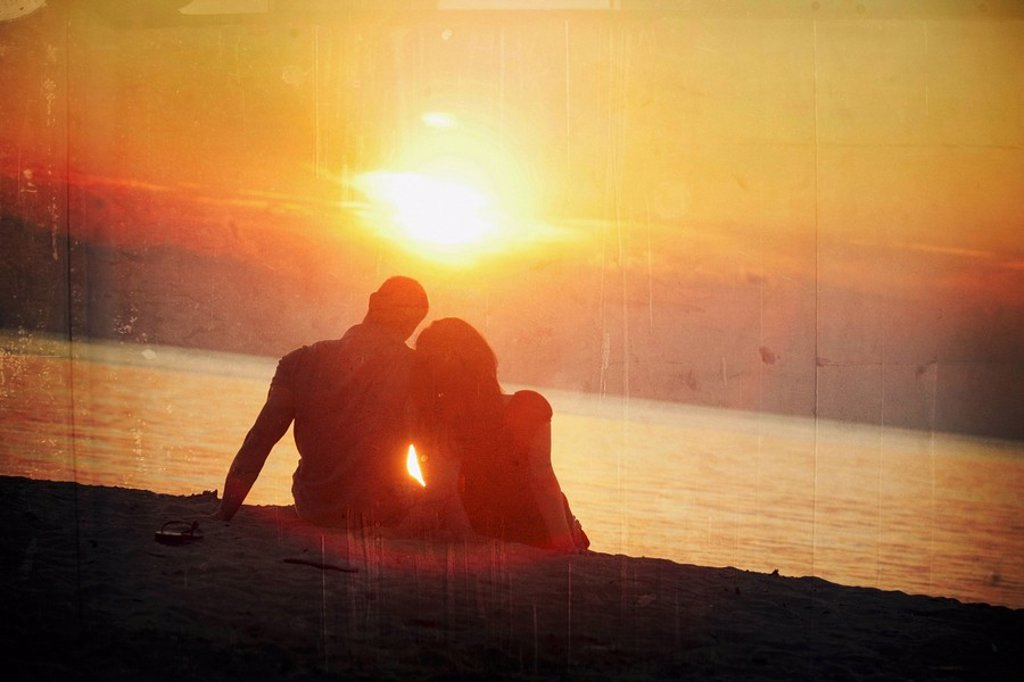 Stock Photo: 1889R-53649 a man and woman sitting on the beach in a sunset