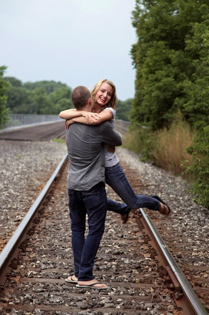 a couple hugging on the train tracks : Stock Photo