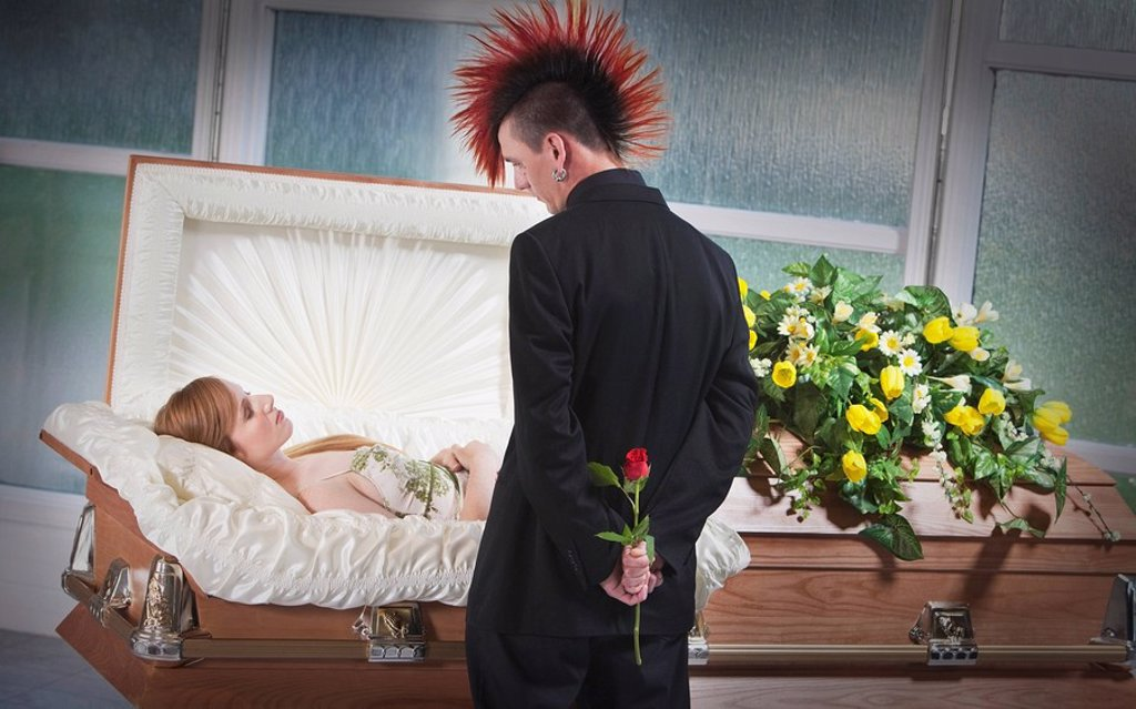 a man holding a rose and viewing a deceased woman laying in a coffin : Stock Photo