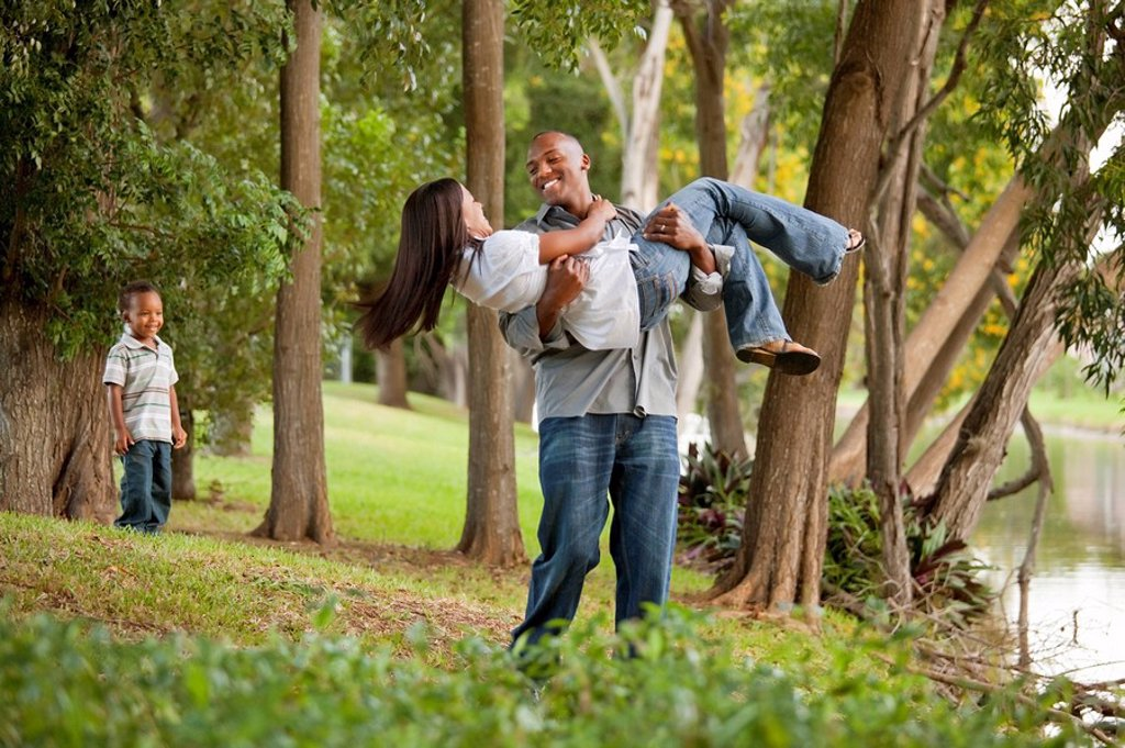 fort lauderdale, florida, united states of america, a couple having fun in a park while their young son watches : Stock Photo