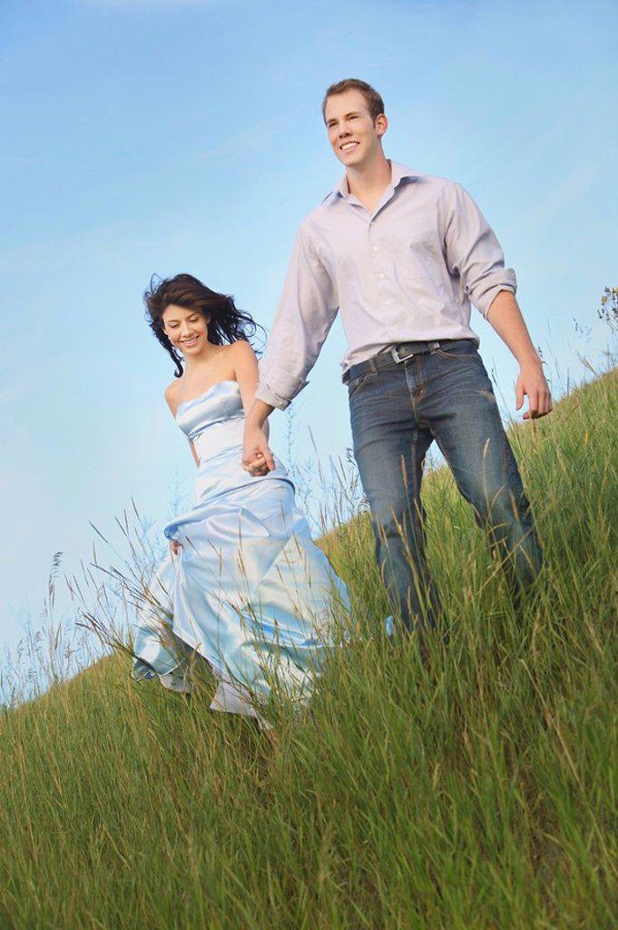 Stock Photo: 1889R-53974 edmonton, alberta, canada, a couple running through the grass