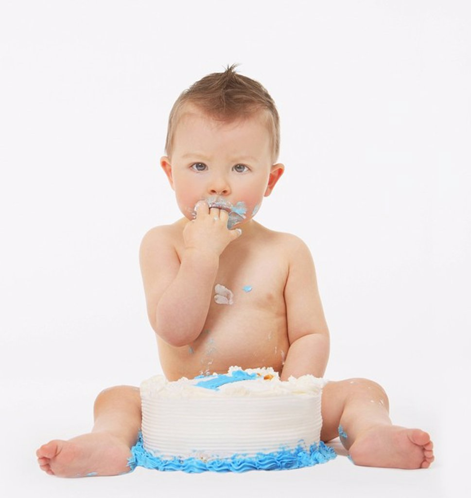 edmonton, alberta, canada, a baby eating birthday cake with his hands : Stock Photo