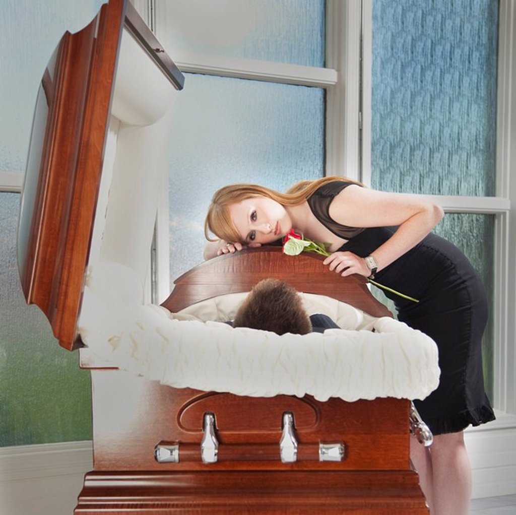 edmonton, alberta, canada, a young woman holds a rose and lays her head on the coffin of a deceased loved one : Stock Photo