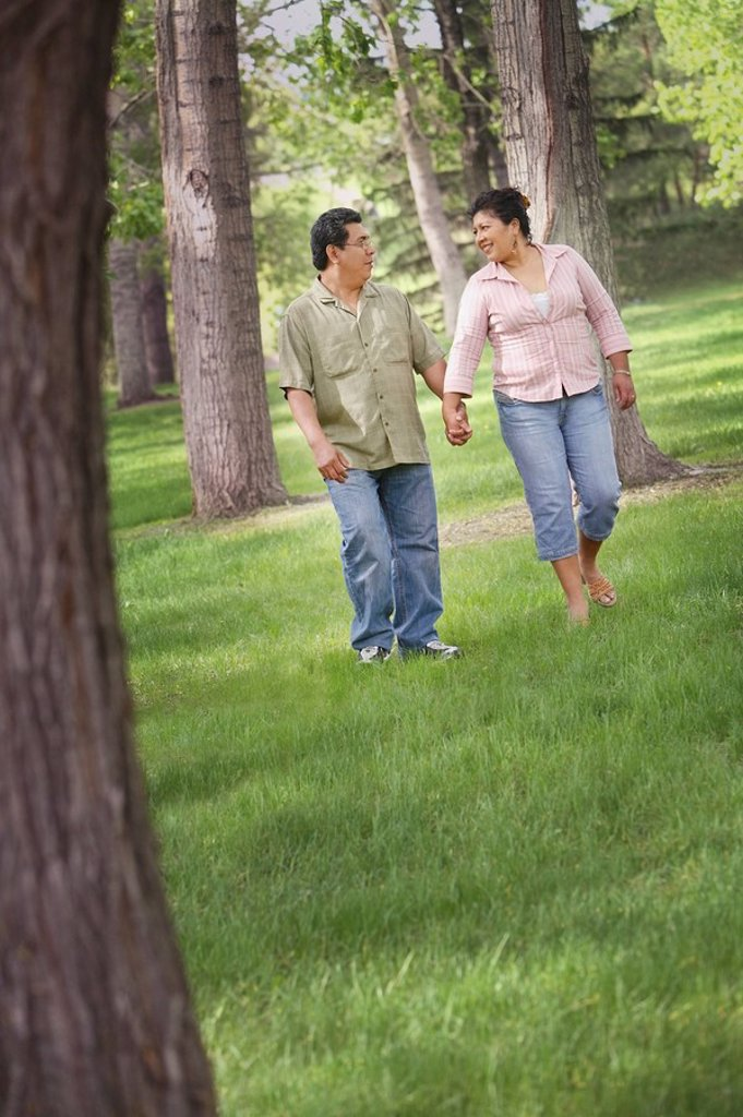 edmonton, alberta, canada, a man and woman walking through a park holding hands : Stock Photo