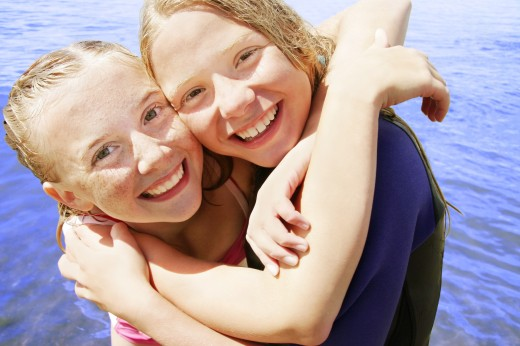 Two girls hug in the water : Stock Photo