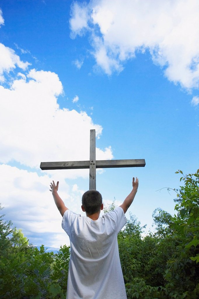 Stock Photo: 1889R-54191 A Teenage Boy With Arms Raised Towards The Cross