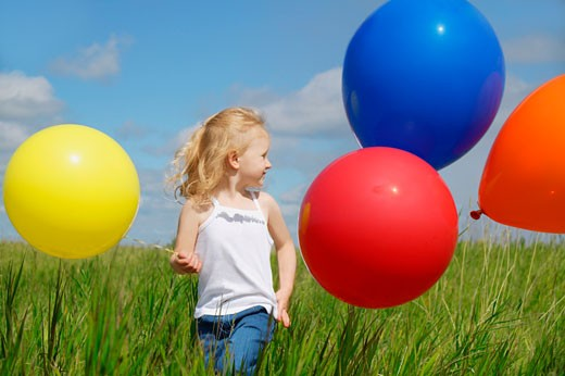 A child holding colorful balloons : Stock Photo