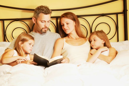 Family in bed reading bible : Stock Photo