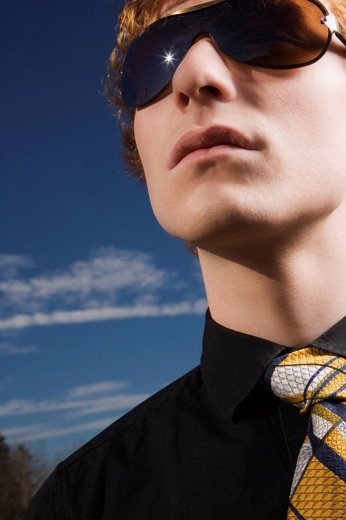 A Young Man Wearing Sunglasses And A Necktie : Stock Photo