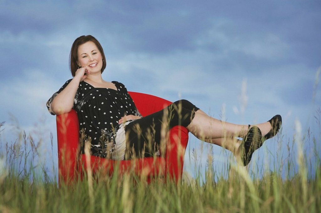 a woman sitting in a red chair in the middle of a field : Stock Photo