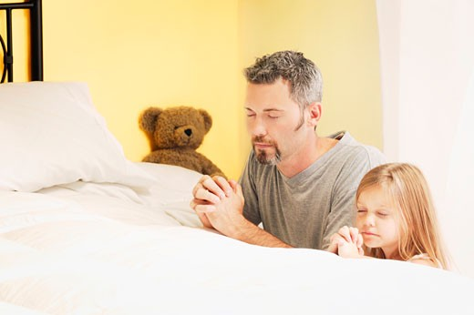 Father praying with daughter : Stock Photo