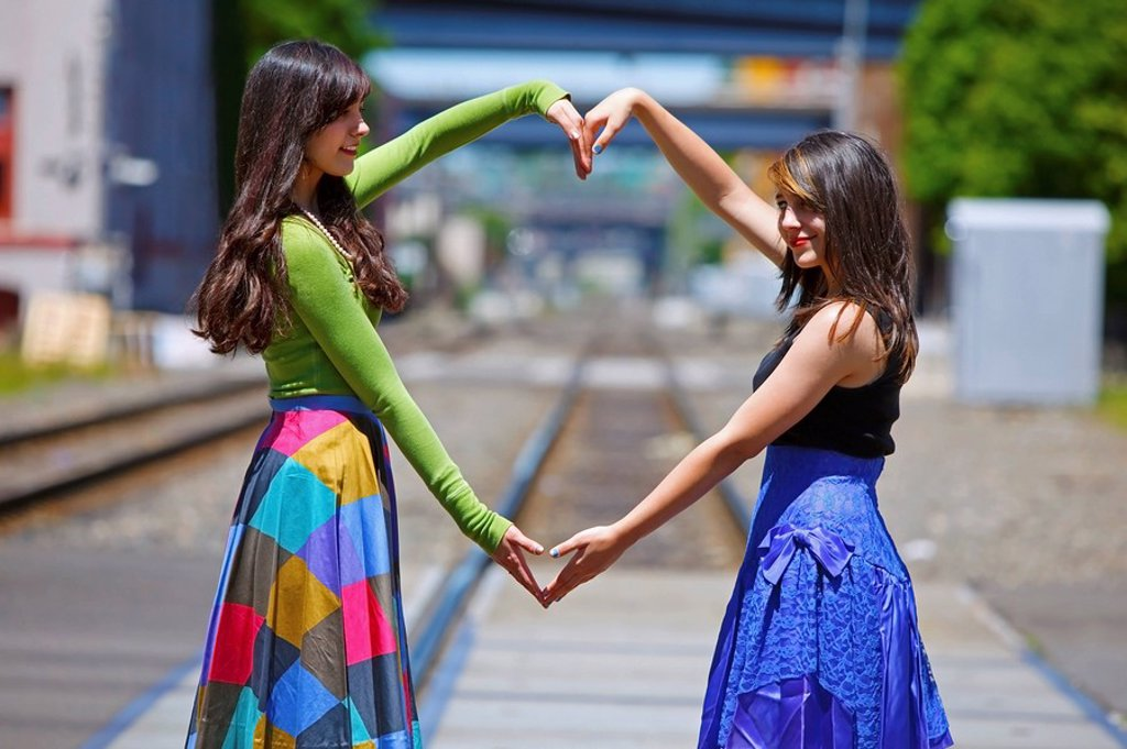 teenage girls forming a heart with their arms, portland, oregon, united states of america : Stock Photo
