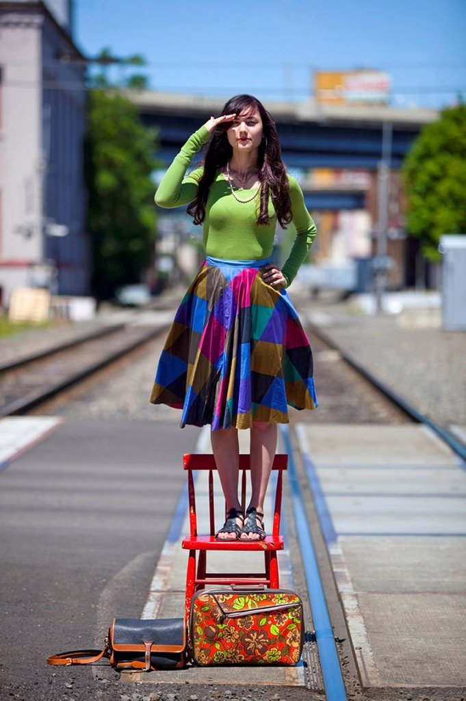 teenage girl standing on a chair looking for the train in downtown: portland, oregon, united states of america : Stock Photo