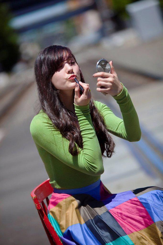 Stock Photo: 1889R-56160 teenage girl applying lipstick, portland, oregon, united states of america