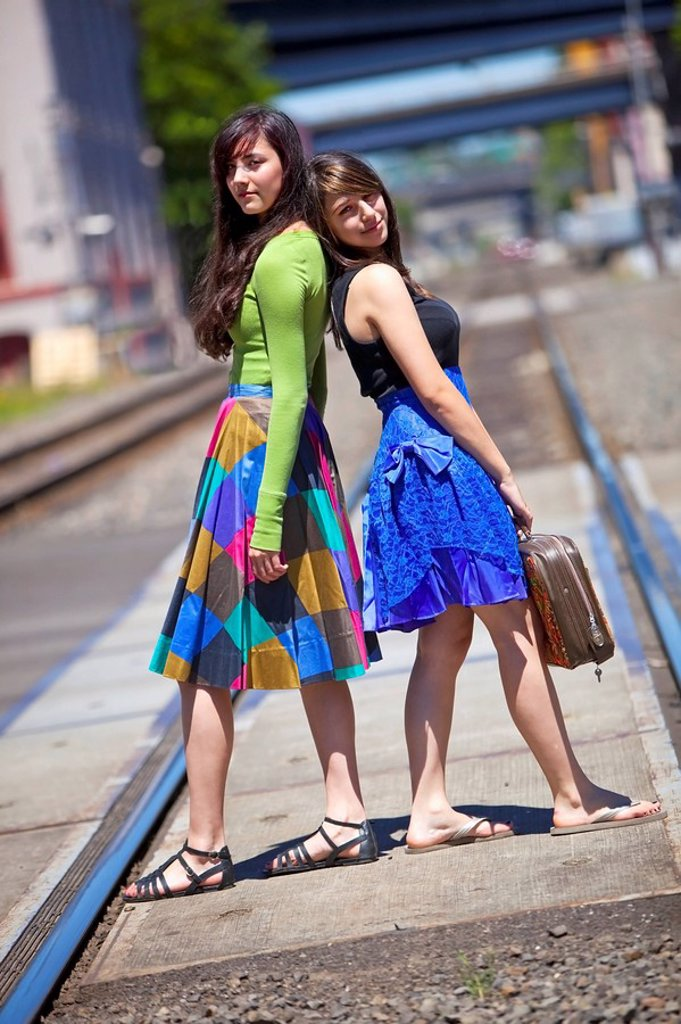 teenage girls standing on the train tracks downtown, portland, oregon, united states of america : Stock Photo