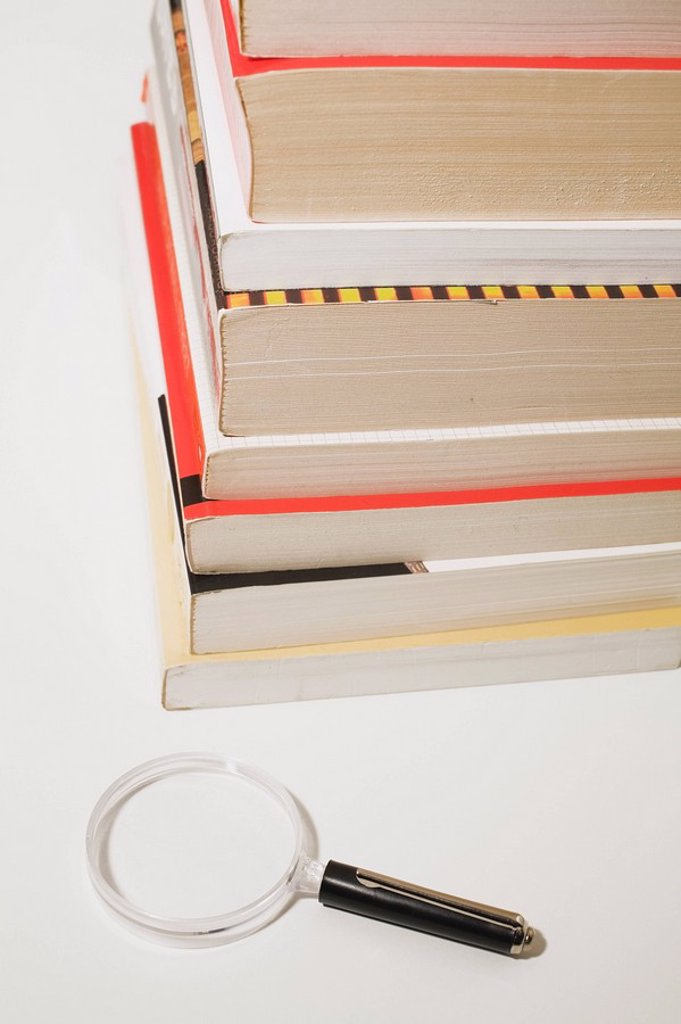 magnifying glass next to a stack of paperback books : Stock Photo