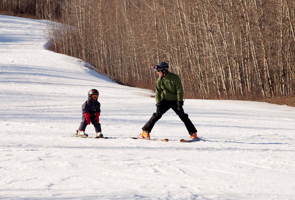 red deer, alberta, canada, a father teaches his young son how to ski : Stock Photo