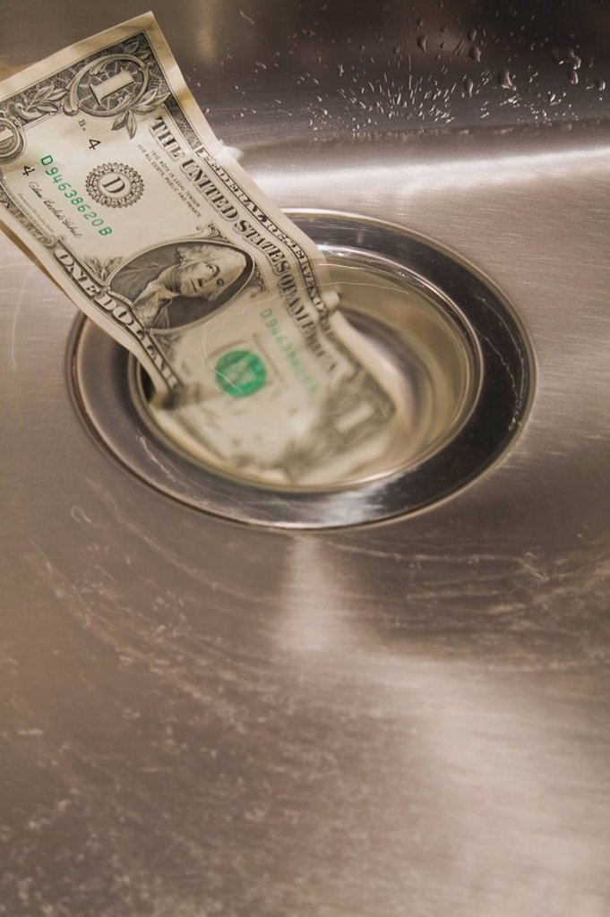 american dollar bill going down the drain in a sink : Stock Photo