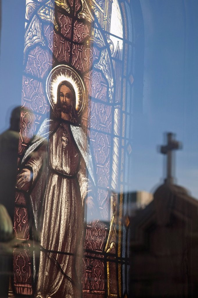 Buenos Aires, Argentina, A Stained Glass Window Depicting Jesus With A Reflection Of A Cross In Recoleta Cemetery : Stock Photo