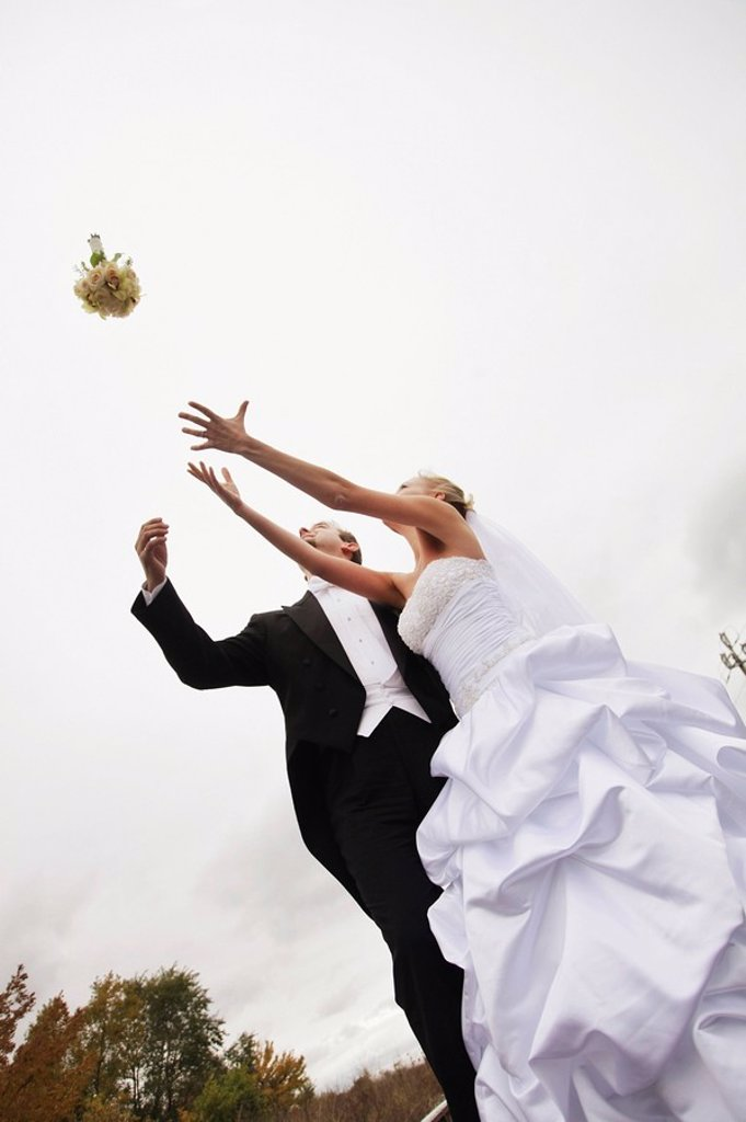 Stoney Creek, Ontario, Canada, A Bride And Groom Trying To Catch A Bouquet : Stock Photo