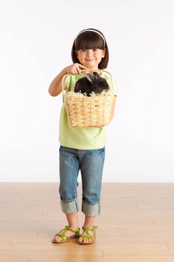 A Girl Holding A Basket With A Rabbit In It : Stock Photo