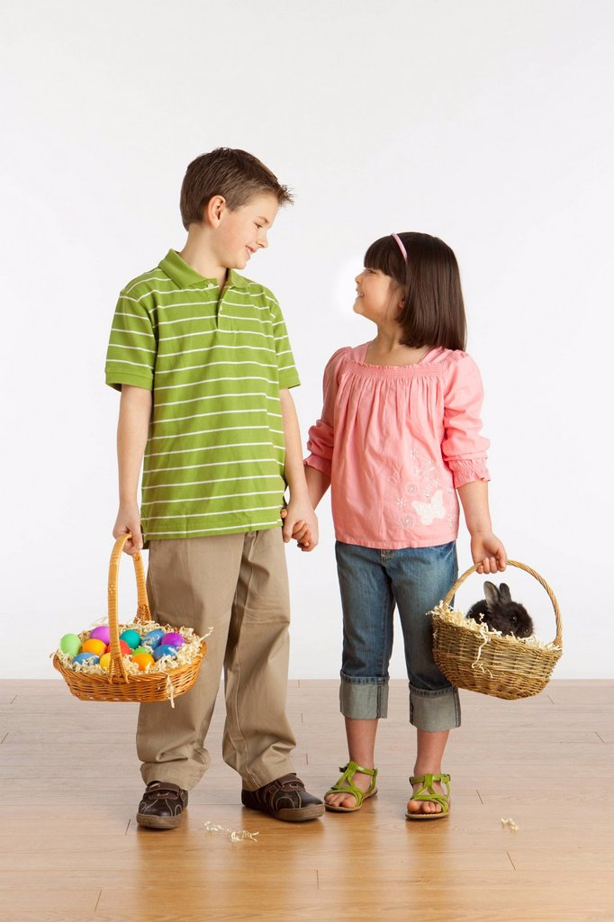 A Boy And Girl Holding Baskets With A Rabbit And Colorful Easter Eggs In Them : Stock Photo
