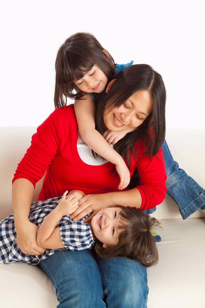 A Mother Playing With Her Two Daughters : Stock Photo
